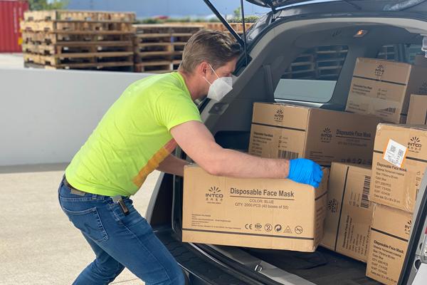 Man wearing PPE unpacking car