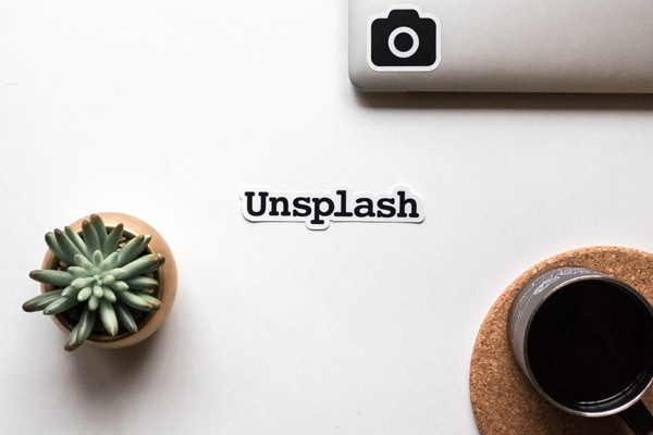 Unsplash logo on a desk with a black coffee and plant